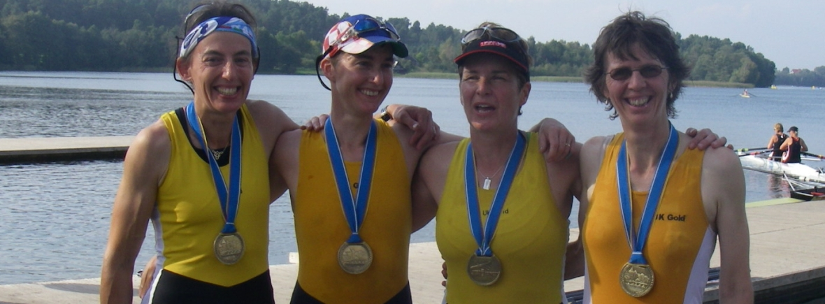 4 women in gold racing vests with medals